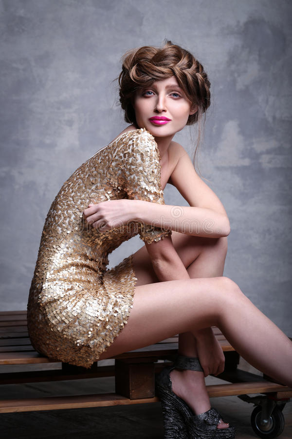 Girl model wearing luxurious gold dress sitting on the wooden stand royalty free stock image