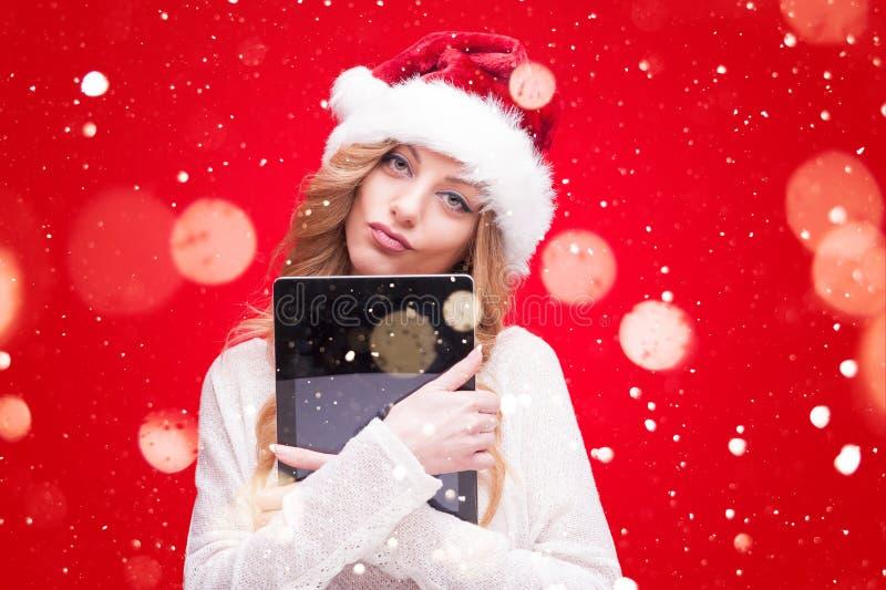 Girl modelo rubio en Santa Hat sobre rojo imagenes de archivo