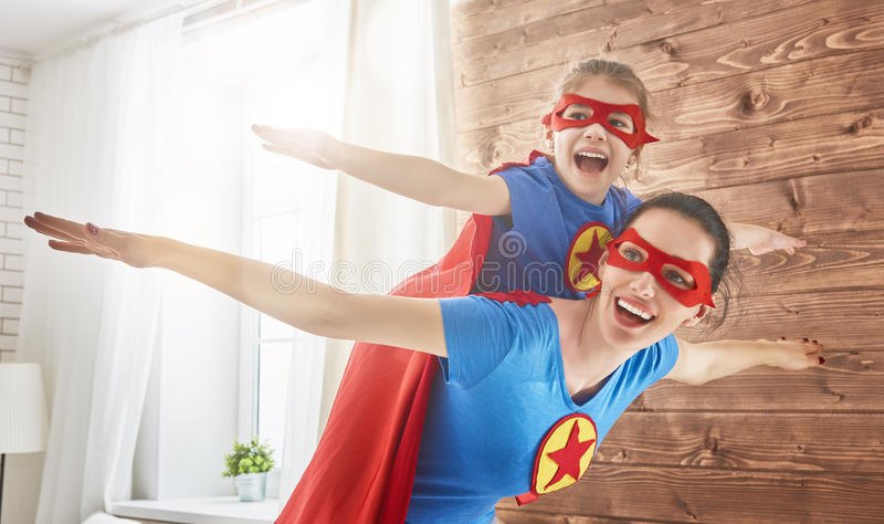 Girl and mom in Superhero costumes stock images