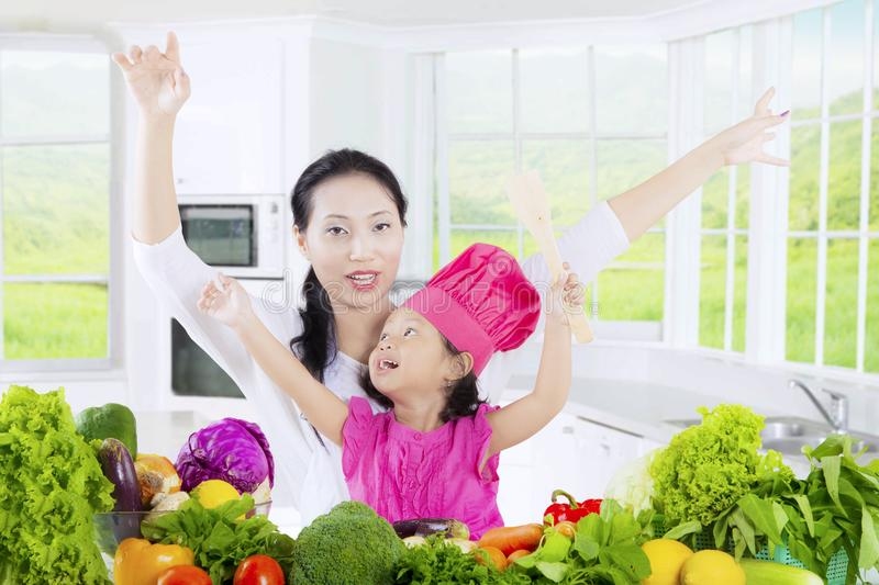 Girl and mom with vegetables in kitchen royalty free stock images