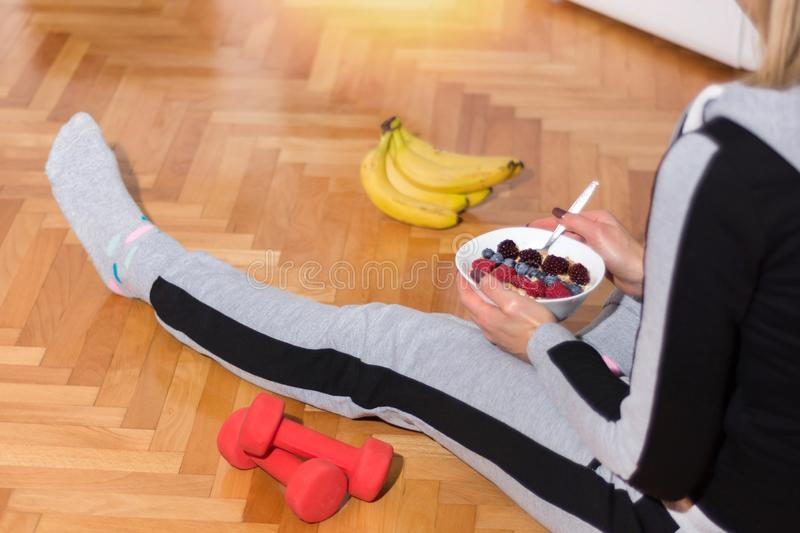 Girl in morning sitting on floor and eating Oats porridge. In bowl after exercises. On floor is red dumbbell and bananas. Health life and food concept. Close up royalty free stock photos
