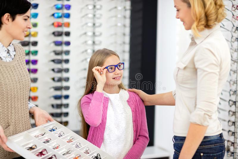 Girl with mother choose new eye frame stock image