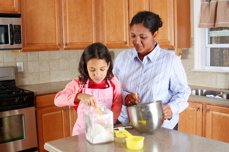 Girl And Mother Cooking Stock Images