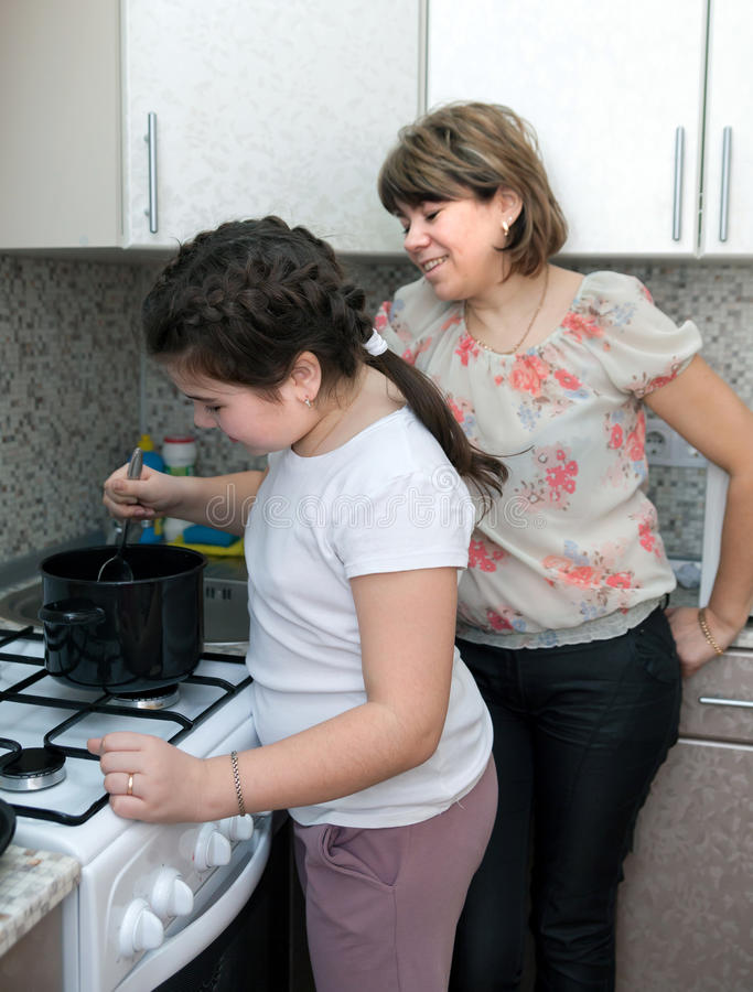 Girl and mother cooking at kitchen stock image