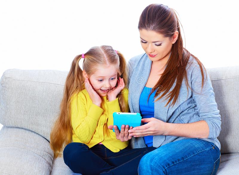 Girl with mother sitting on sofa using tablet royalty free stock photography