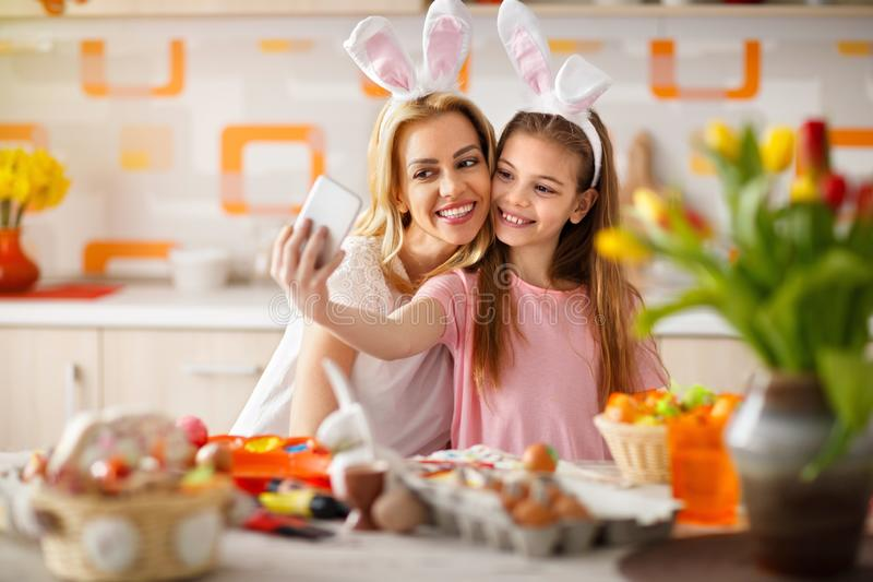 Girl with mother taking selfie with cell phone royalty free stock photography