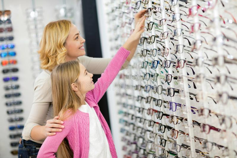 Girl with mother try eye frames stock images