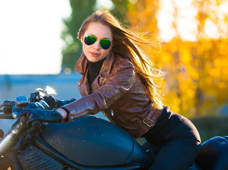 Girl on motorcycle, brown jacket, half height royalty free stock photos