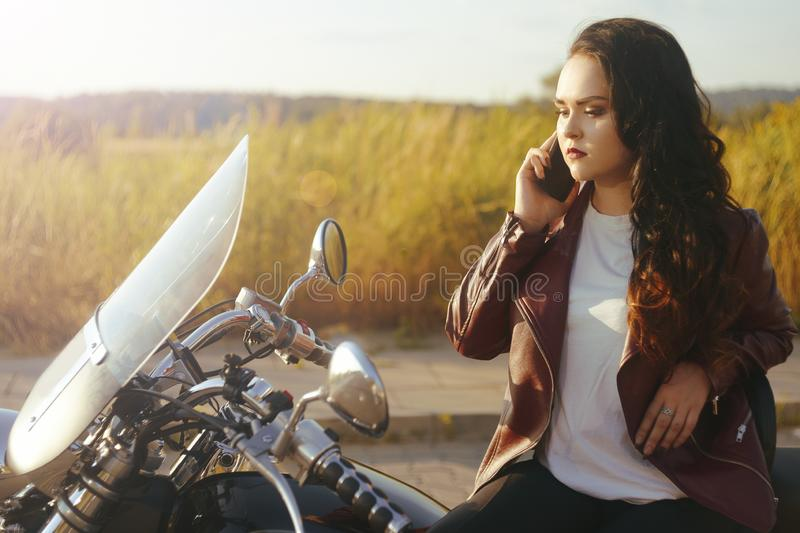 Girl on a motorcycle at sunset. Girl in the field near the bike speaks on the phone. Woman in the journey with the phone, roaming. Girl calls vehicle rescue royalty free stock photos