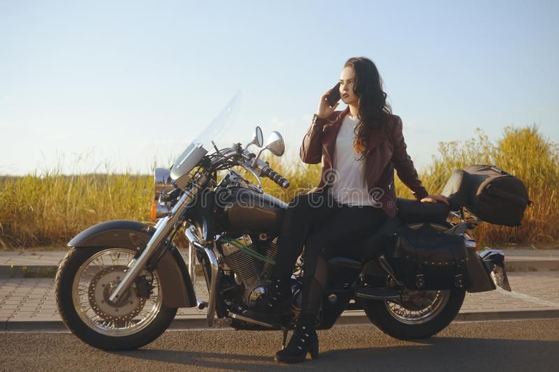 Girl on a motorcycle at sunset. Girl in the field near the bike speaks on the phone. Woman in the journey with the phone, roaming. Girl calls vehicle rescue stock photos