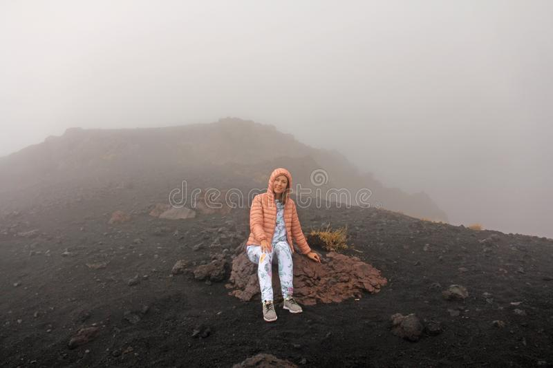The girl on Mount Etna. The Etna volcano crater. Black Volcanic Earth, Volcanic Lava and Stones. Dense Fog on Mount Etna. Place stock photo