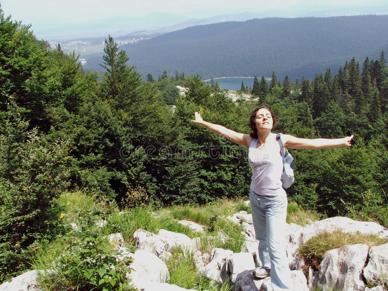 Girl at the mountain top with arms wide spread stock image
