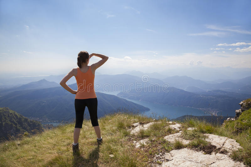 Girl on mountain top looking. Woman standing on mountain top looking at mountain landscape and blue sky royalty free stock image