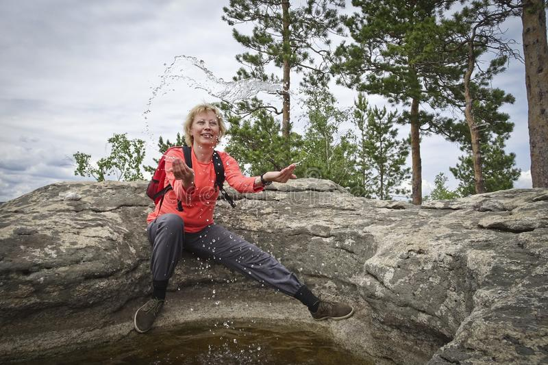 A girl in the mountains throws water up from a puddle. royalty free stock photo