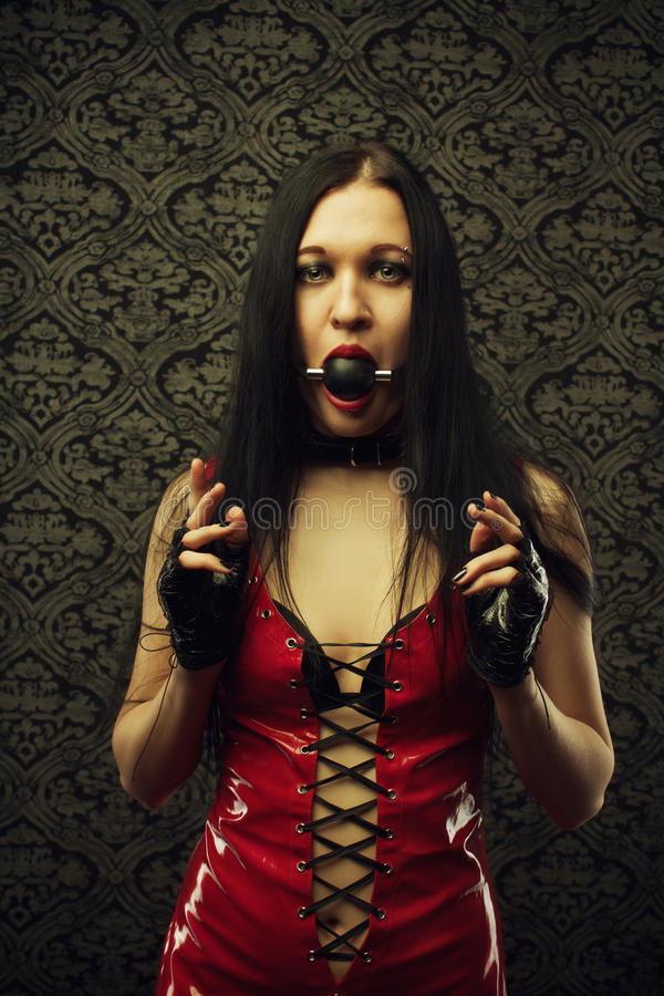 Girl with mouth gag. Pretty girl in red latex dress with mouth gag stands in an empty room royalty free stock photo