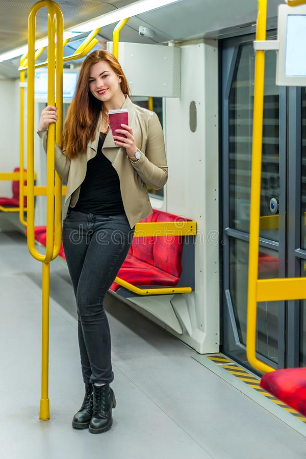 The girl with mug of coffee inside an empty subway train royalty free stock photo