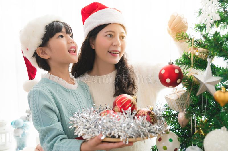Girl with mum are decorating a Christmas tree stock photos