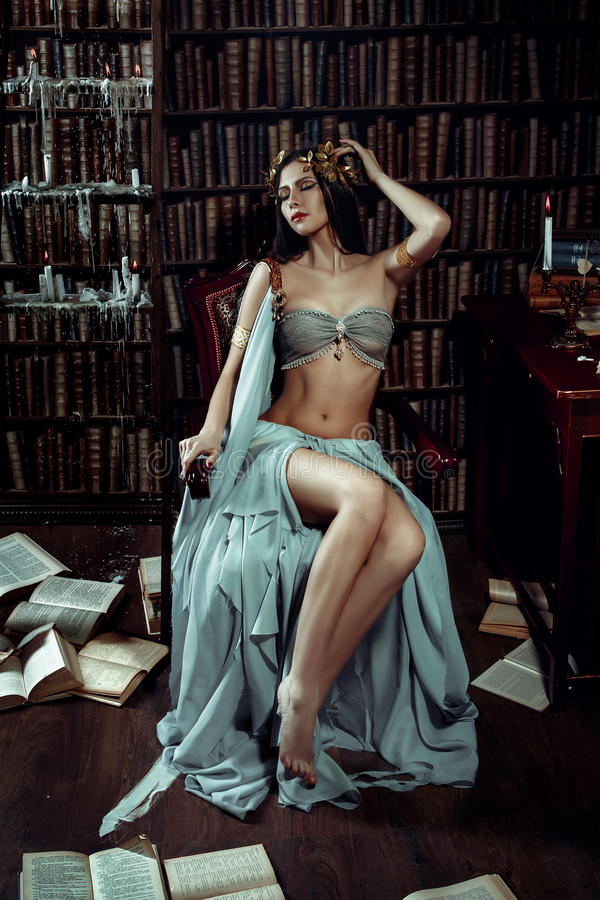 Girl muse of the poet. In Greek robes standing in the room full of books and inspiring fashion creative color toning stock photo