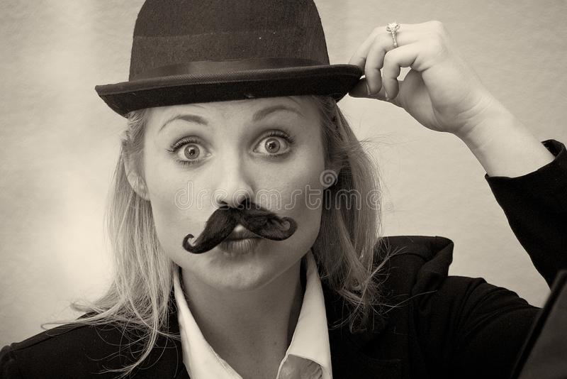 Girl with mustache and bowler hat. Portrait of young blonde woman wearing bowler hat and sporting black mustache stock image