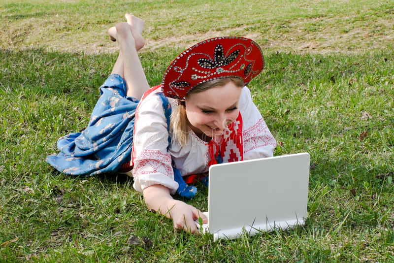 Girl in national clothes with a laptop on the grass. Russian girl in national clothes with a laptop on the green grass stock photo