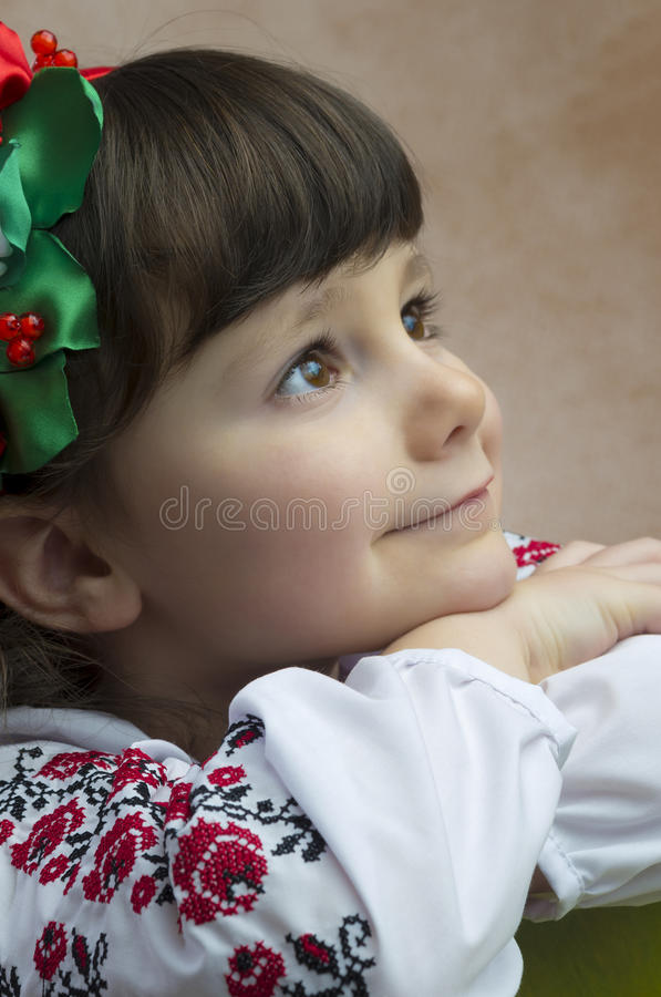 Girl in national costume. Six years old dreaming girl in national Romanian costume stock photo