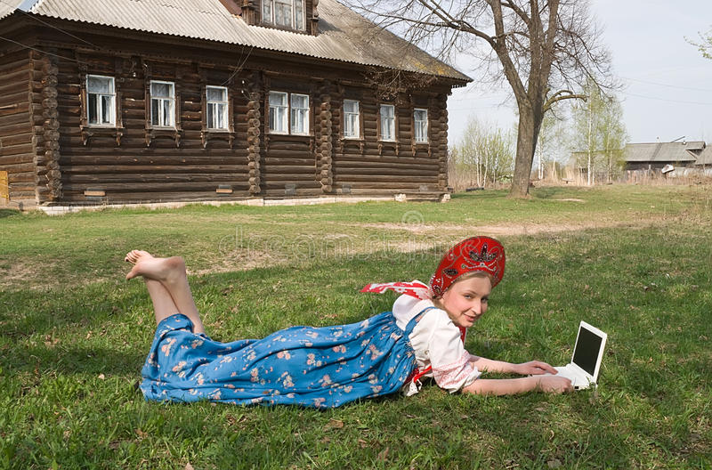 Girl in national dress with a computer. Lies in the grass stock photos