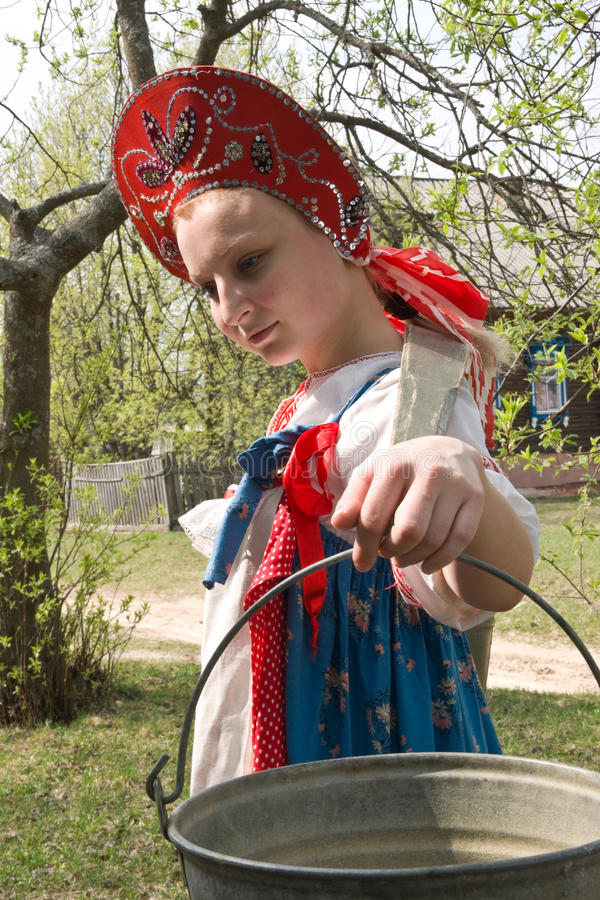 Girl in national dress with a yoke. And buckets for water is stock image
