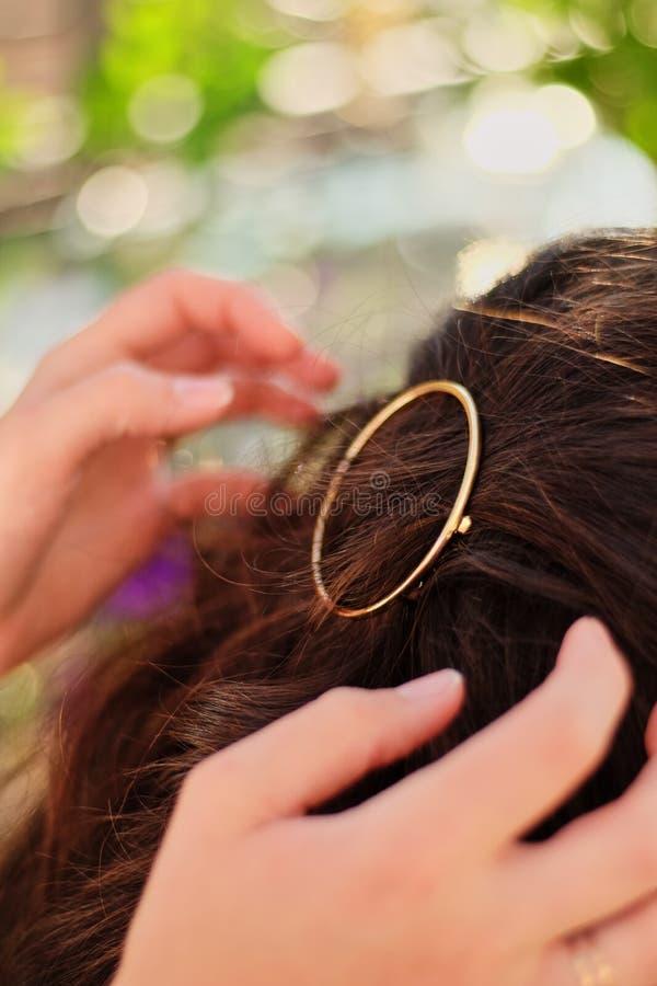 Girl at nature making headdress straightens the hair pin. Girl on nature, straightens the hair pin royalty free stock photos