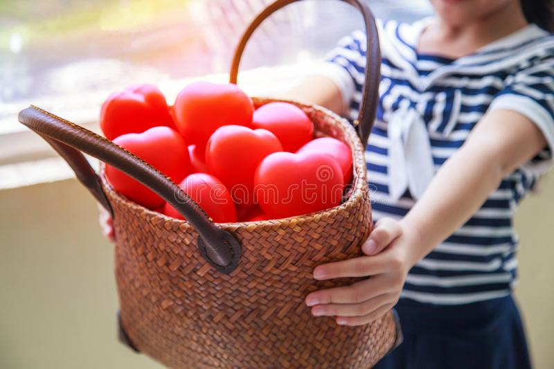 Girl in navy blue striped dress handing basket of red hearts represents helping hands, family support, morale, purity, innocence, royalty free stock photo
