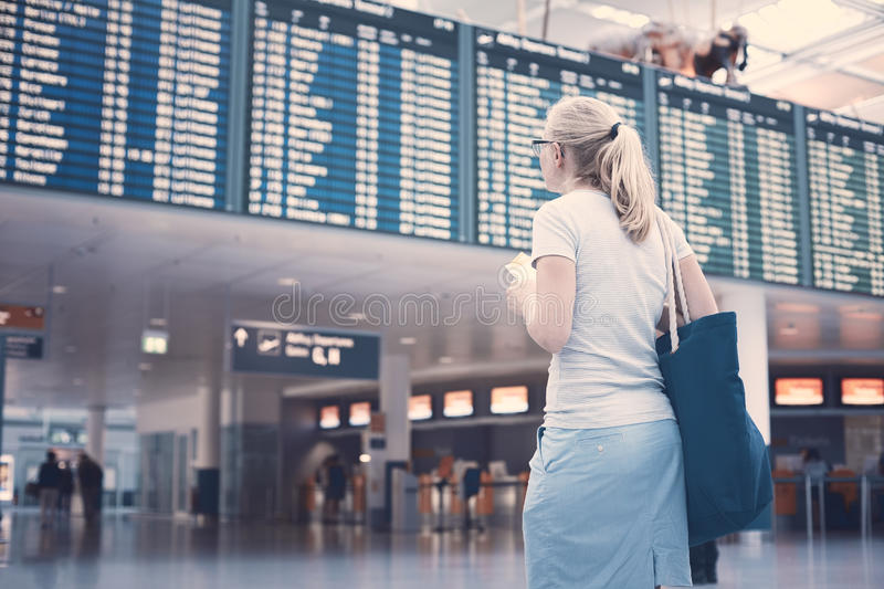 Girl near airline schedule stock photography