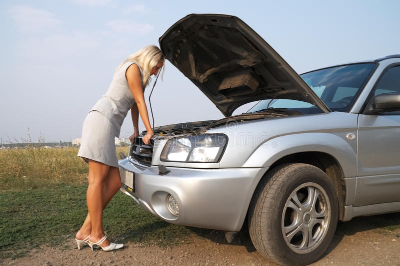 Girl near the car. The blonde looks blankly under the hood of the broken car stock photos