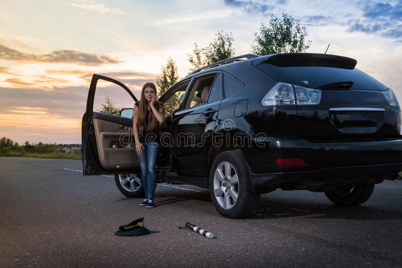 Girl near the car looking with horror at the cap and baton of a police officer. Female driver hiting a COP. Russia royalty free stock photo