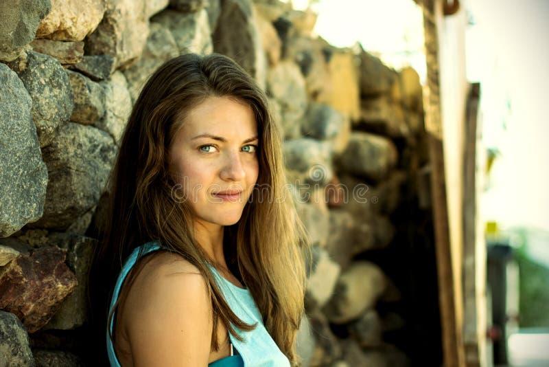 Girl near the stone wall royalty free stock photography