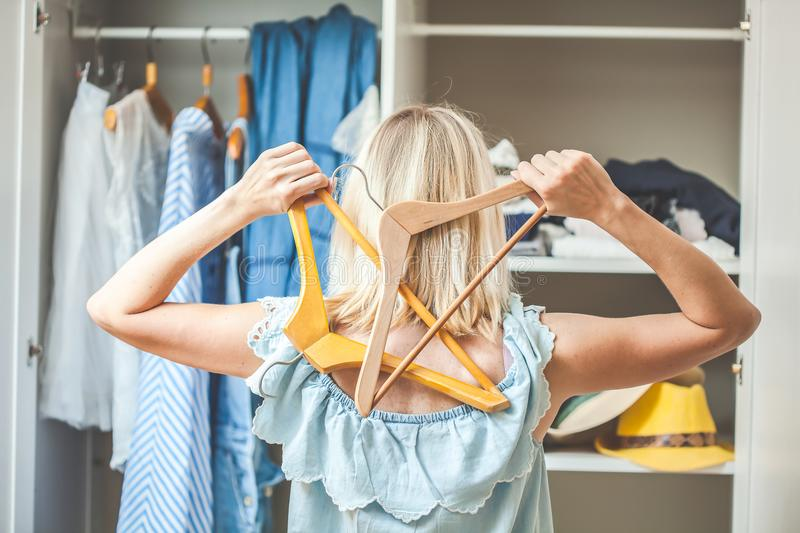 Girl near a wardrobe with clothes can not choose what to wear. Heavy Choice Concept has nothing to wear royalty free stock images