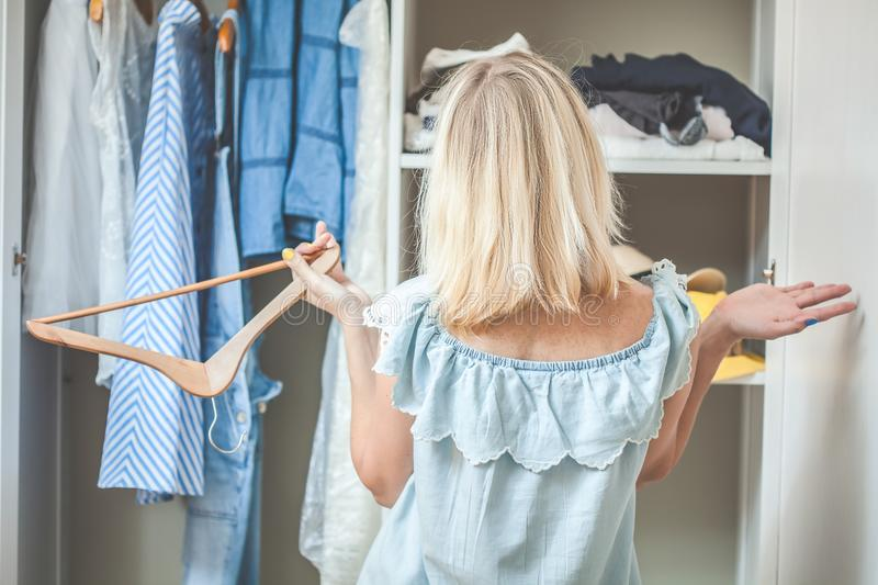 Girl near a wardrobe with clothes can not choose what to wear. Heavy Choice Concept has nothing to wear royalty free stock photos