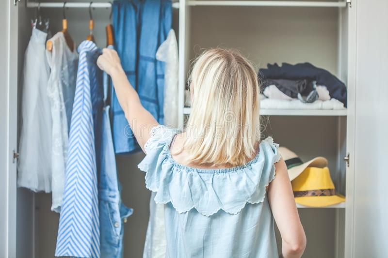 Girl near a wardrobe with clothes can not choose what to wear. Heavy Choice Concept has nothing to wear stock image