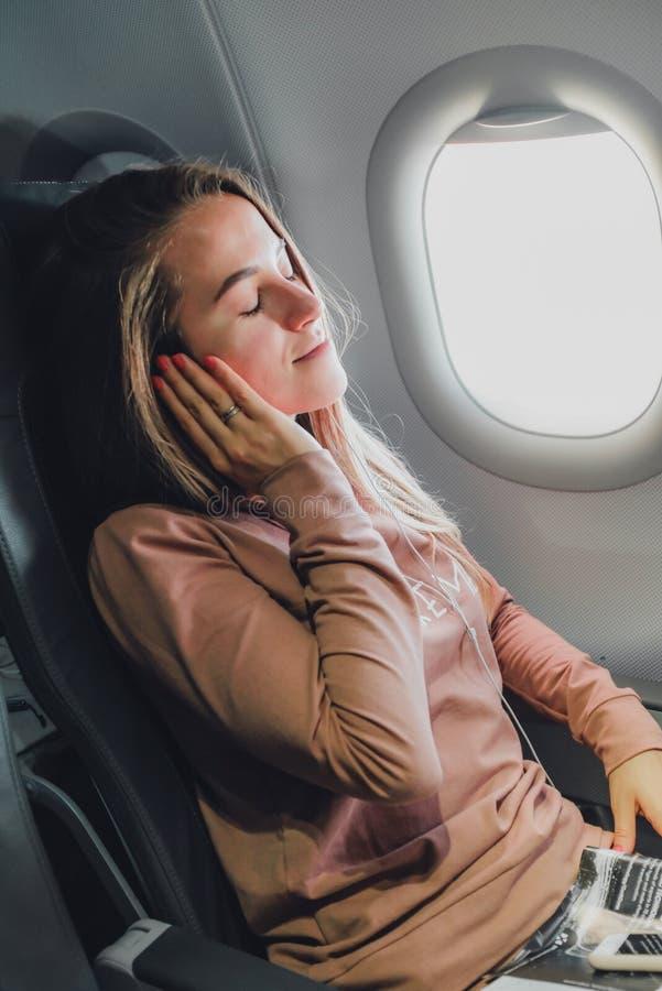 Girl near the window in airrplane listening music stock image