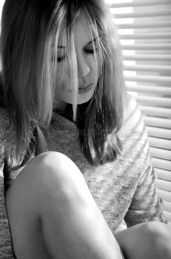 Girl near the window. Beautiful girl near the window closed louver on a sunny day royalty free stock photos