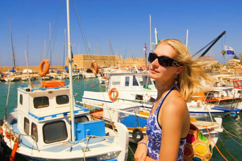 Girl near the yacht club. Beautiful blond girl in sunglasses near the yacht club royalty free stock photography