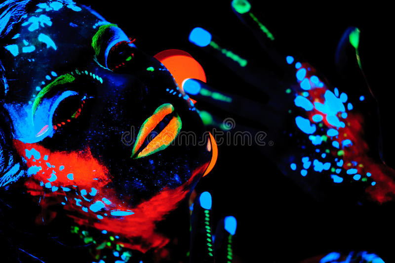 Girl with neon paint body art portrait. Studio shot stock photos