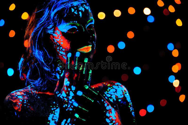 Girl with neon paint bodyart portrait. Studio shot stock image