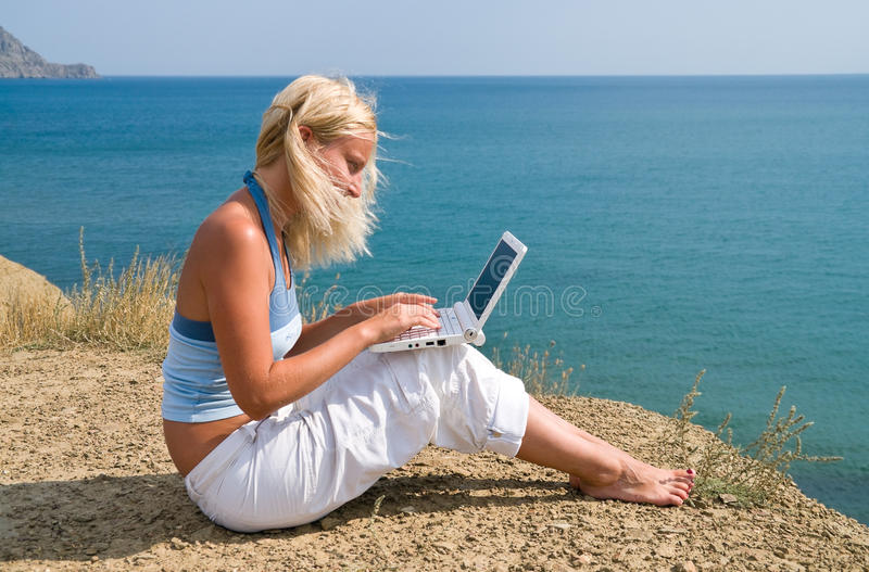 Girl with netbook. Girl with a netbook sitting on the bank against the sky royalty free stock photography