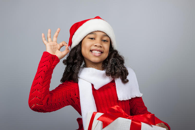 Girl with a New Year gift. Joyful girl in a cap of Santa Claus. Dark-skinned girl with a New Year gift. Joyful girl in a cap of Santa Claus on a gray background royalty free stock images