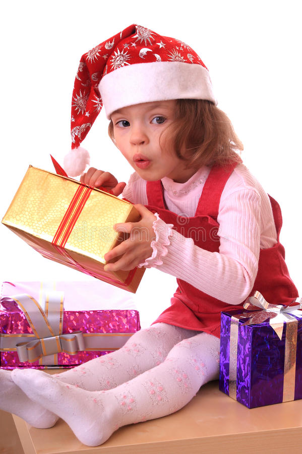 Girl in a new-year hubcap. Little girl in a new-year hubcap with gifts stock image