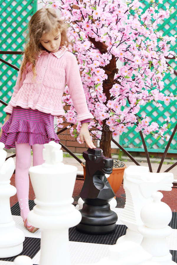 Girl next to artificial cherry blossom touches big chess pieces. On big chessboard in park. Focus on tree royalty free stock photography