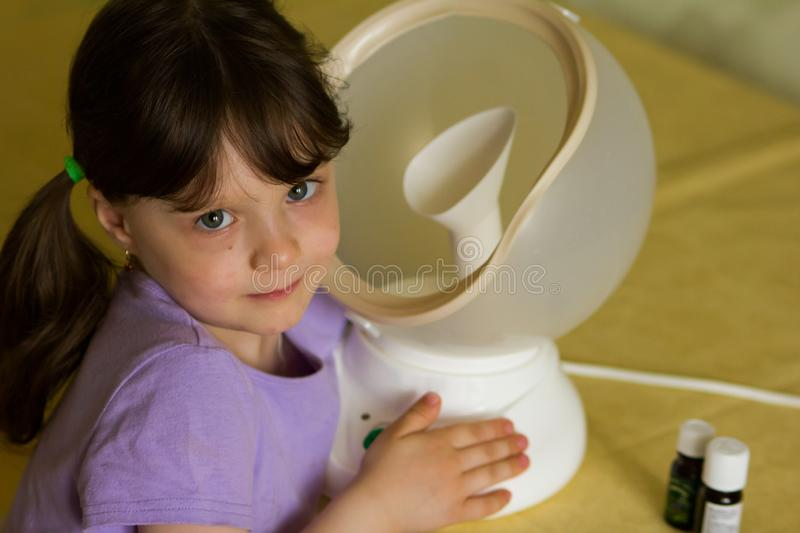 The girl next to the round white steam inhaler is treated for flu and cold. On the table are bottles of essential oils and. Medicines. horizontal photo stock photography