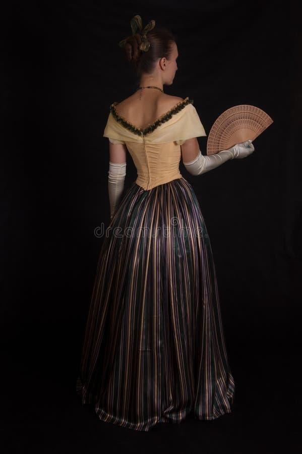 Girl in nineteenth century dress. Standing girl in nineteenth century dress isolated on black royalty free stock photo