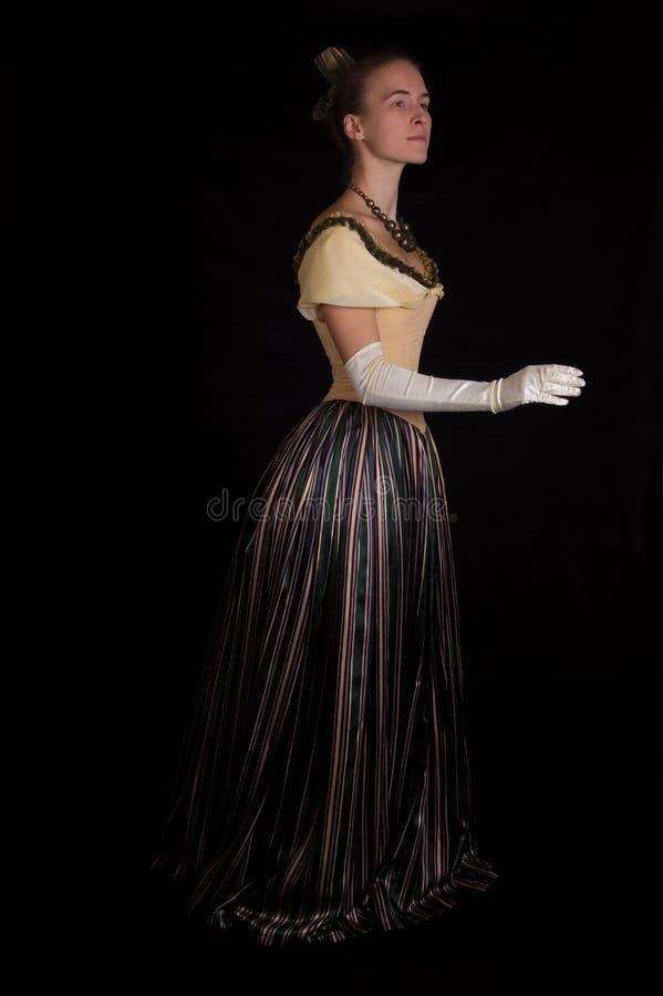 Girl in nineteenth century dress. Standing girl in nineteenth century dress isolated on black royalty free stock image
