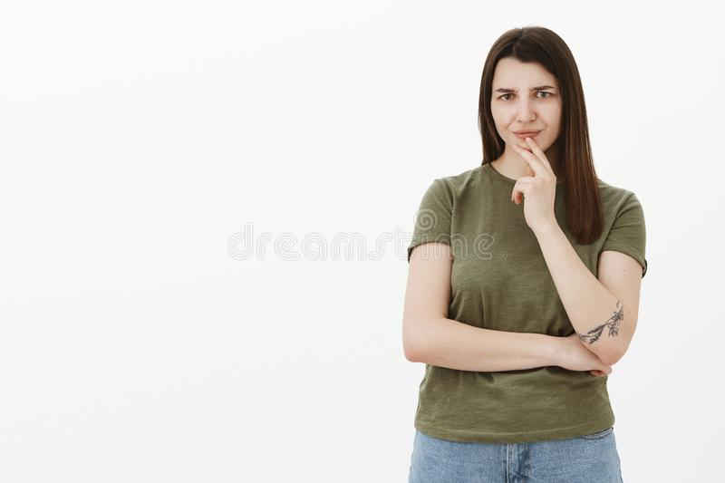 Girl not liking what hears, frowning and wrinkling nose from dislike and confusion holding hand above lip squinting at. Camera and cross one arm over body royalty free stock images
