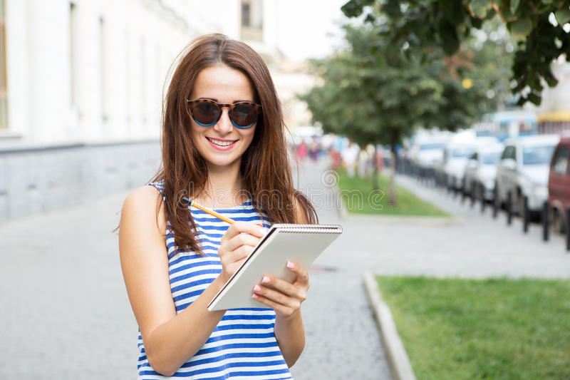 Girl with a notebook and a pencil on the street. Girl with a notebook on the street royalty free stock photo